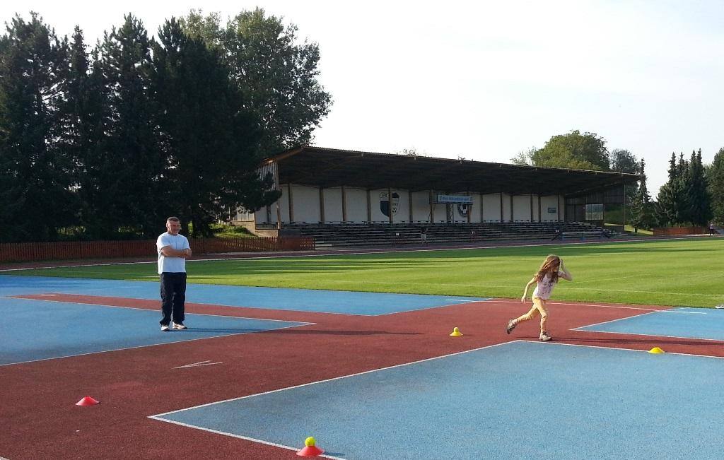 Trenér dohlíží na malé atlety.